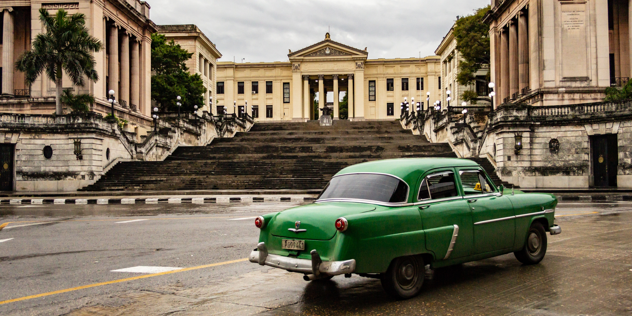 Looking towards the steps of the Universidad de la Habana during a break in the rain as a car passes by.